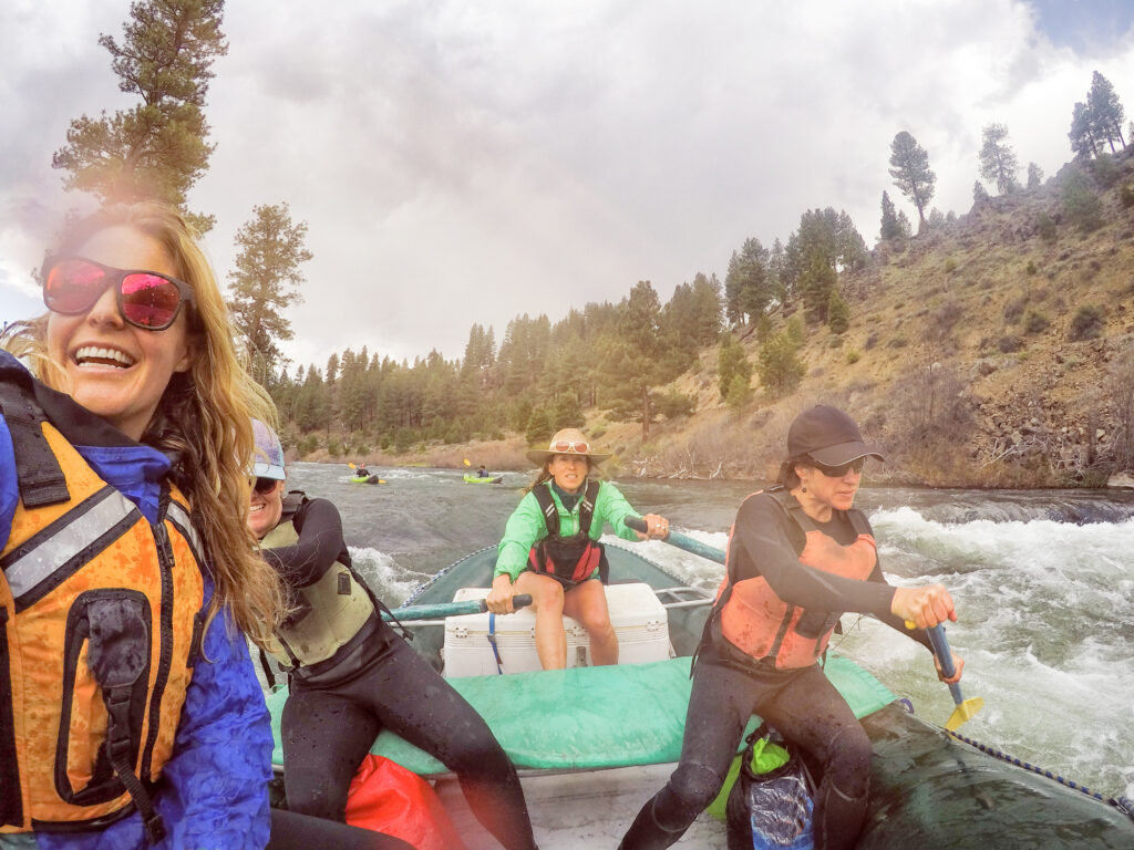 Strong, independent women on a rafting trip rowing in big rapids. Friends in their 40s rafting the Truckee River.